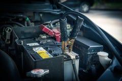 Het belasten van autobatterij met de verbindingsdraadkabels van de elektriciteitstrog stock foto