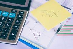 Het belastingswoord, kalender met herinnert notauiterste termijn en calculator op lijst eraan stock foto's