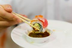 Het belemmeren van Sushibroodje met Kani, Komkommer en Avocado op bovenkant met Zalm en Ikura Het onderdompelen in Sojasaus en Wa Stock Foto
