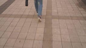 Het benenmeisje in jeans gaat op de weg naar het park stock footage