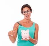 Het benieuwd zijnde donkerbruine spaarvarken van de vrouwenholding Stock Fotografie