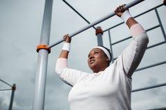 Het bepaalde te zware Afrikaanse vrouw praktizeren trekt in openlucht oefening uit stock afbeelding