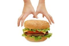 Het bereik van handen voor een hamburger Stock Foto