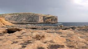 Het berglandschap van de kust van San Lawrenz met een mening over stormachtige golven, die tegen de rotsen en de klippen, Gozo ve stock footage