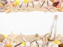 Het bericht in een glasfles ligt op het zandstrand met zeeschelpen en zeester royalty-vrije stock afbeeldingen