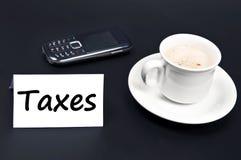 Het bericht van belastingen op bureau met koffie royalty-vrije stock foto's