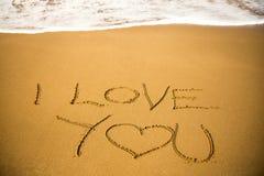 Het bericht van de liefde dat in zand wordt geschreven Stock Foto's