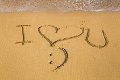 Het bericht van de liefde dat in zand wordt geschreven Stock Afbeeldingen