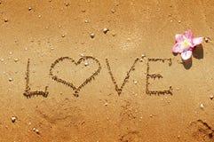 Het bericht van de liefde in zand wordt geschreven dat Royalty-vrije Stock Foto's