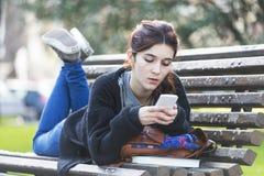 Het bericht van de meisjeslezing op telefoon, adolescentie lifestile concept, ou Stock Afbeelding