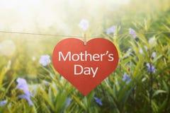 Het bericht van de moedersdag met gevoelde harten die met wasknijpers hangen Stock Foto's