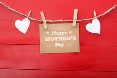 Het bericht van de moedersdag met gevoelde harten die met wasknijpers hangen Royalty-vrije Stock Foto's