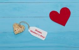 Het bericht van de moedersdag met harten over blauwe houten raad stock foto's