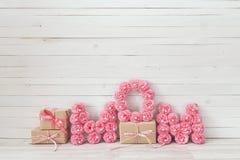 Het bericht van de moedersdag van roze document bloemen over witte houten beer stock afbeeldingen
