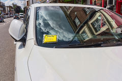 Het bericht van de sanctielast (parkerenboete) maakte aan voorruit van witte auto vast die in hoofdstraat Londen Engeland wordt g stock afbeelding