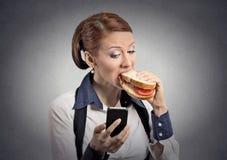 Het bericht van de vrouwenlezing op smartphone die sandwich eten stock foto's