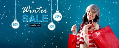 Het bericht van de de winterverkoop met vrouwenholding het winkelen zakken stock foto's