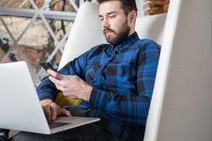 Het bericht van de zakenmanlezing op mobiele telefoon tijdens webinar op laptop computer stock afbeelding