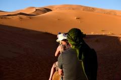 Het berijden op de ruggen van de dromedarissen door de duinen van de woestijn Royalty-vrije Stock Afbeeldingen