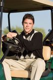 Het berijden van de golfspeler in golfkar Stock Afbeelding