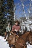 Het Berijden van de man en van de Vrouw Paarden in de Sneeuw stock foto's