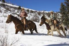 Het Berijden van de man en van de Vrouw Paarden in de Sneeuw royalty-vrije stock afbeelding