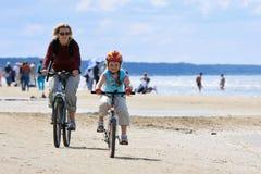 Het berijden van de moeder en van de dochter langs het strand Stock Foto's