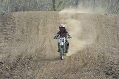 Het Berijden van de Raceauto van de motocross onderaan een Heuvel van het Vuil Royalty-vrije Stock Foto's
