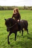 Het berijden van de vrouw paard op gebied stock foto