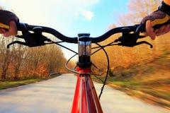 Het berijden van een fiets op een weg stock foto