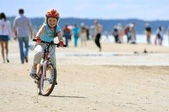 Het berijden van het meisje met fiets langs het strand Stock Foto's