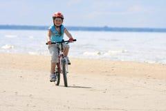 Het berijden van het meisje met fiets langs het strand Stock Fotografie