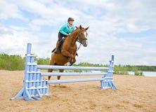 Het berijden van het meisje paard en het springen stock foto
