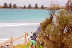 Het Berijden van vaderand son bike naast de Oceaan royalty-vrije stock fotografie