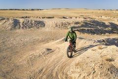 Het berijden van vette fiets in badlands stock foto