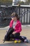 Het berijdende skateboard van het modieuze meisjekind in stad Stock Foto's
