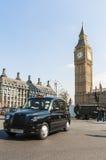 Het beroemde zwarte cabine drijven door Huizen van het Parlement Stock Afbeeldingen