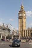 Het beroemde zwarte cabine drijven door Huizen van het Parlement Stock Foto's