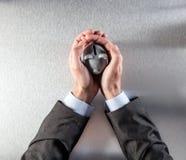 Het beschermen van zakenmanhanden die een veilige spaarpot voor rijkdom houden Stock Afbeelding