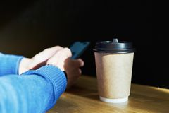 Het beschikbare glas van het ambacht pakpapier met koffie, zakenman smartphone gebruiken terwijl het hebben van rust, onderbrekin royalty-vrije stock afbeeldingen