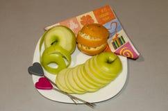 Het besnoeiingsfruit op een oranje knipsel van de plaatappel door segmenten stock fotografie