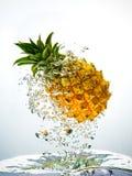 Het bespatten van de ananas in water stock foto