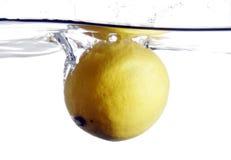 Het bespatten van de citroen in water stock afbeeldingen