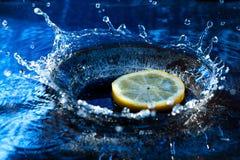 Het bespatten van de citroen in water Stock Foto