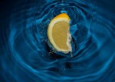 Het bespatten van de citroen in water stock afbeelding