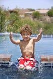Het Bespatten van de jongen in een Pool stock afbeelding