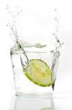 Het bespatten van de Komkommer van plakken in water Stock Afbeeldingen