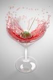 Het bespatten van de olijf in een cocktailglas Stock Foto