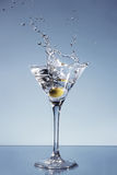 Het bespatten van de olijf in een glas van Martini Stock Fotografie