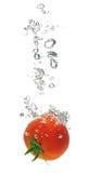 Het bespatten van de tomaat in water Stock Afbeeldingen